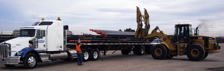 PIPE BEING LOADED ON A TRAILER SEMI TRUCK
